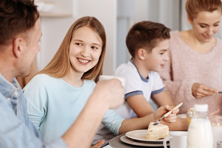 cheeful: Cheeful girl enjoying dinner with her family Stock Photo