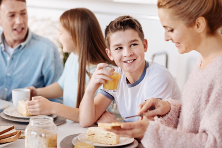 Cheerful boy having breakfast with his family Stock Photo