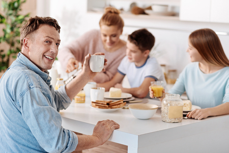 upbringing: Cheeful man having breakfast with his family