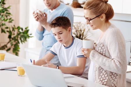 diligente: Madre solícita revisando la tarea de su hijo