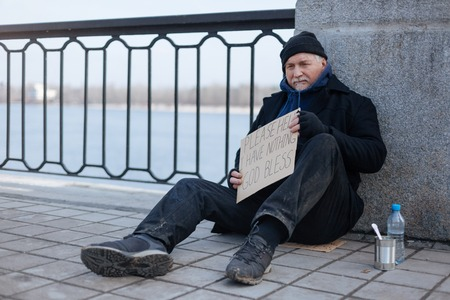 prejudice: Homeless gray-haired man sitting on the tile