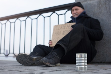 prejudice: Close up picture of tin standing near homeless man