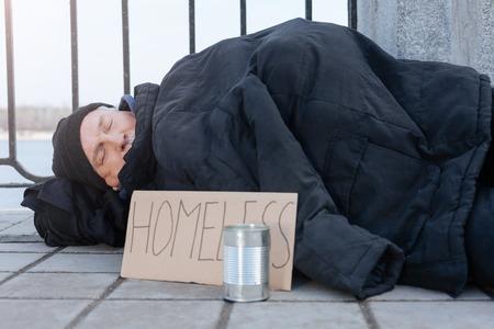 Homeless man lying on cold pavement