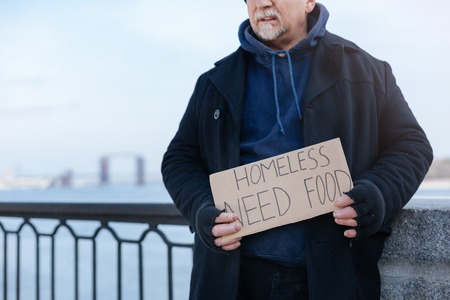 dismissed: Homeless pensioner standing with paper in his hands