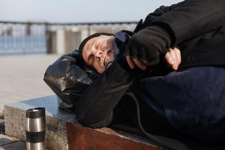 Sleepy man lying on the bench