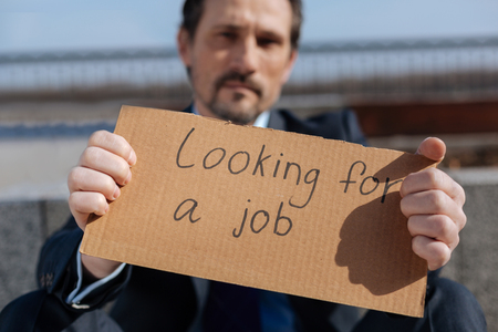 unemployed dismissed: Handsome bearded man holding poster in his hands