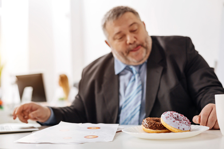 burned out: Hungry burned out employee thinking about his lunch break Stock Photo