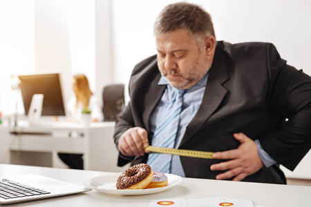 Unhealthy obese employee looking concerned