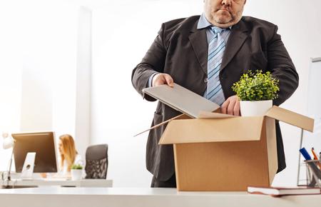Bezorgde vermoeide werknemer die zijn dingen inpakken