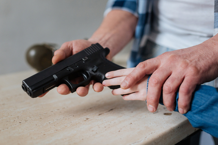 Handgun being in hands of a young girl Stock Photo