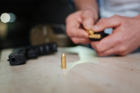 Selective focus of a bullet standing on the table Stock Photo