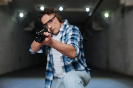 Serious skilled marksman shooting at you Stock Photo