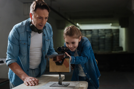 Pleasant caring father spending time with his daughter with a rifle Stock Photo