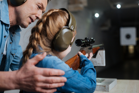 Pleasant cheerful man helping his daughter in shooting