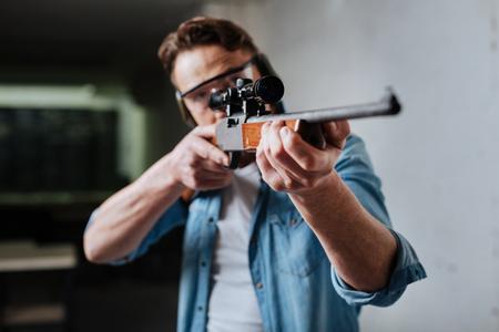 Nice pleasant man developing his shooting skills