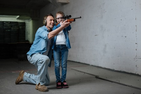 Good looking joyful girl learning to shoot with her father Stock Photo