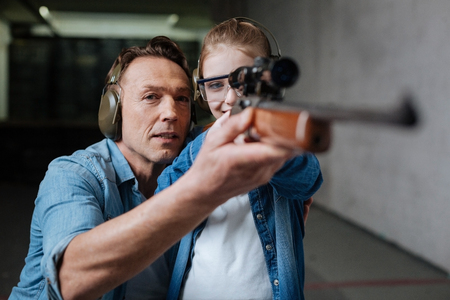 Cheerful exited girl wearing protective glasses with her father, in rifle shooting training