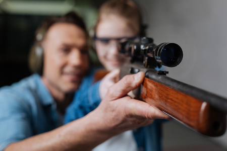Selective focus of a gun with an optical sight, father and her daughter in background Stock Photo