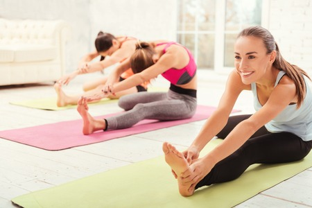 lie forward: Happy female gym visitor leaning while stretching Stock Photo