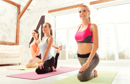Group of ladies stretching themselves at gym.