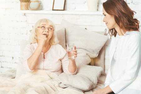 social work aged care: Responsible nurse caring about retired pensioner at home