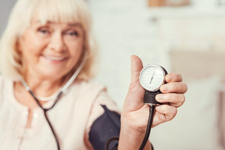 prophylaxis: Glad old lady using tonometer at home Stock Photo