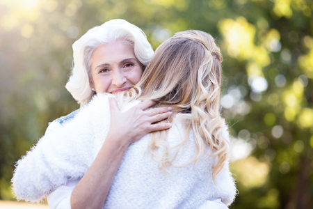 Attractive pensioner hugging mature daughter outdoors