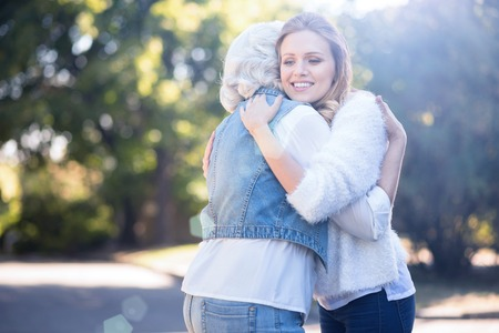 Sincere young woman hugging old mother outdoors