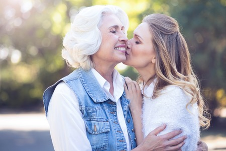 Positive woman kissing on the cheek elderly mother in the park
