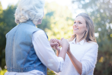 Kind young woman holding hands with grandmother in the park