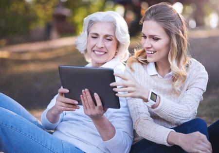 Active woman enjoying picnic with old mother in the park