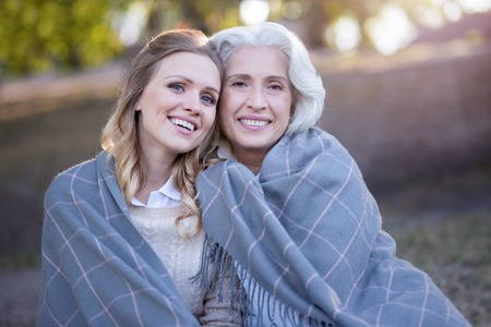 gerontology: Happy woman hugging retired mother at the picnic Stock Photo