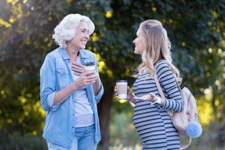 Joyful pregnant woman enjoying conversation with aged mother outdoors