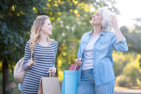 Charismatic old woman enjoying purchases with pregnant daughter outdoors Stock Photo