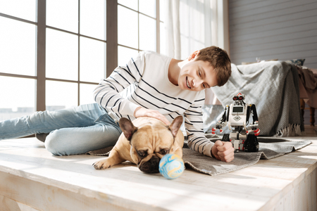 boyhood: Thoughtful dog lying near his young master