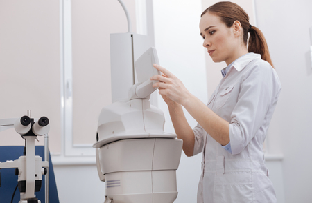health professional: Serious female doctor choosing the settings