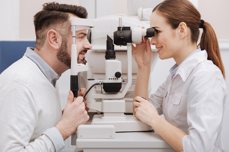 Cheerful delighted man having his eyes tested