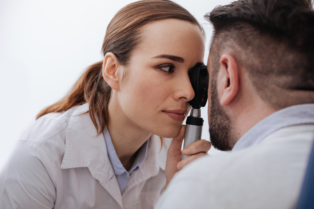 Pleasant pretty woman holding an ophthalmoscope