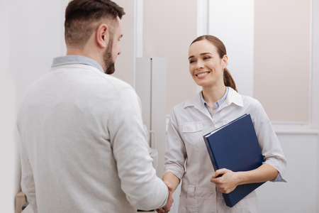 Nice delighted doctor and patient shaking hands Stock Photo