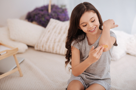 elbow band: Joyful child treating her wound on the elbow at home