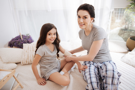 Cheerful young mother and daughter enjoying medicine at home Stock Photo
