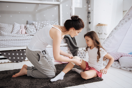 Delighted young mother bandaging her kid at home Stock fotó