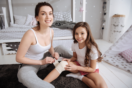 Cheerful mother enjoying first aid help with daughter at home Stock Photo