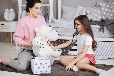 Young mother and little daughter enjoying role games at home Stock Photo