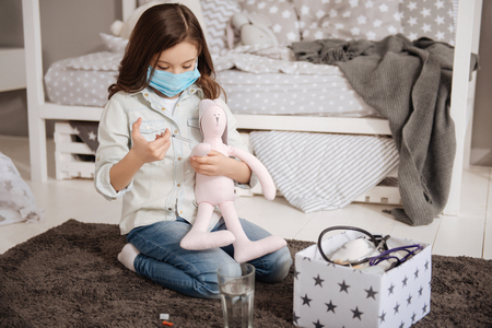 treating: Caring little girl treating favorite toy in the bedroom