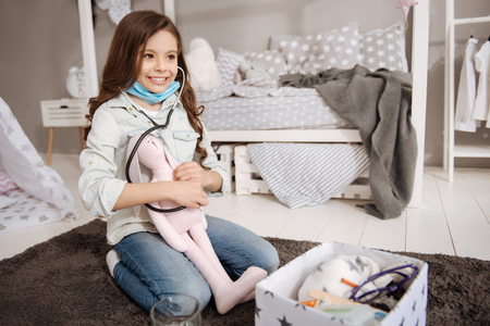 Smiling girl curing plush bunny in the bedroom
