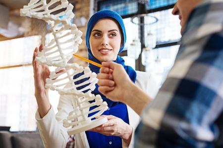 Positive international students studying DNA model Stock Photo