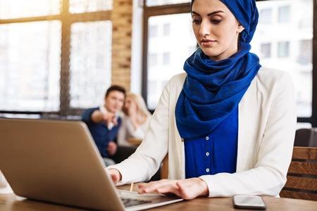 intolerancia: Pleasant muslim businesswoman working on the laptop