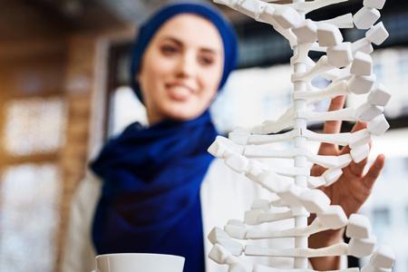 genomics: Selective focus of DNA model in hands of muslim student