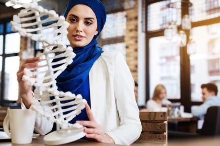 genomics: Curious female muslim student holding DNA model